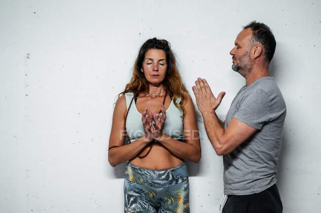 На білому тлі з закритими очима стоїть чоловік і жінка з молитовної асани. — стокове фото