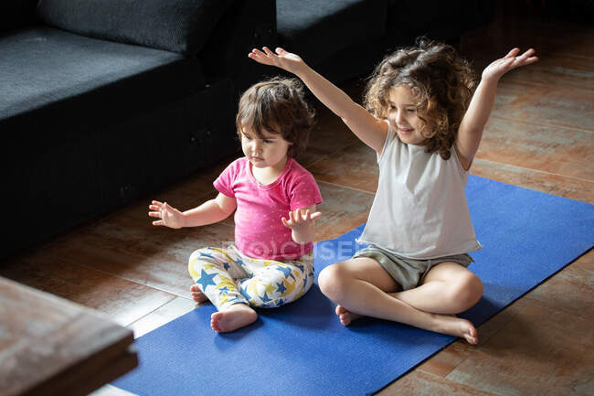 High angle of positive little sisters sitting in lotus pose with outstretched arms while watching video tutorial and practicing yoga together in living room at home — Stock Photo