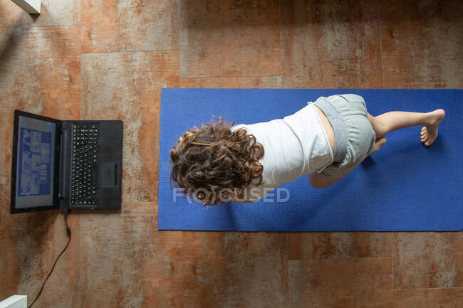 Back view of unrecognizable little girl watching online video tutorial on laptop while sitting on mat and learning yoga pose at home — стоковое фото