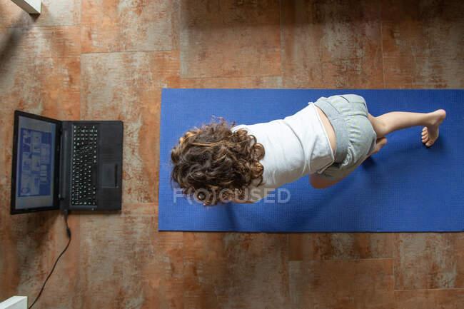 Vista posterior de una niña irreconocible viendo video tutorial en línea en el portátil mientras está sentada en la esterilla y aprendiendo a hacer yoga en casa - foto de stock