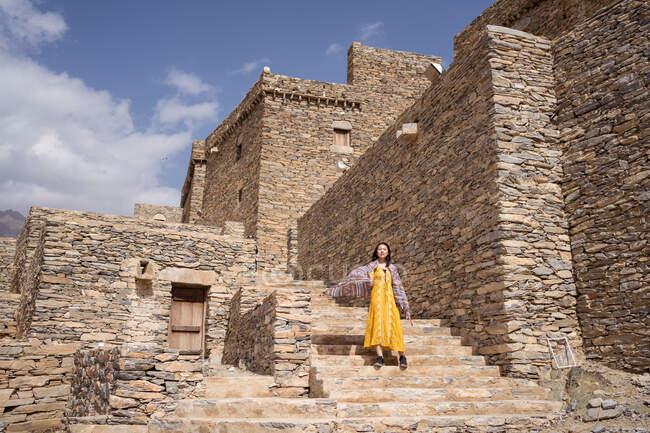 Viajero femenino étnico en traje casual de pie en las escaleras de piedra de la vieja aldea de mármol en Al Bahah en el caluroso día de verano - foto de stock