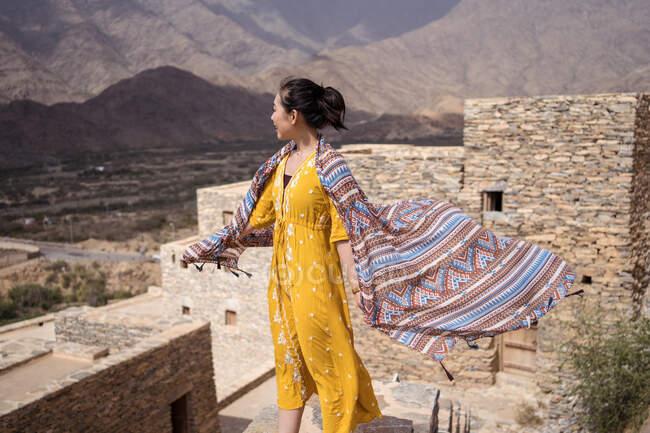 Monumental edificio antiguo con el turista femenino remoto que sale de la puerta en vestido amarillo mientras disfruta de un día soleado caliente en Marble Village en Al Bahah - foto de stock