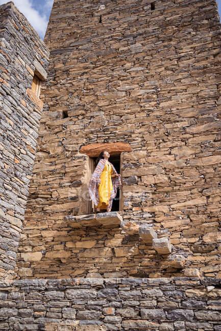 Desde abajo del monumental edificio antiguo con la remota turista femenina que sale de la puerta en vestido amarillo mientras disfruta de un día soleado caliente en Marble Village en Al Bahah - foto de stock