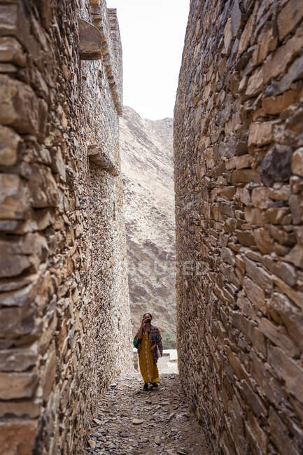 Distant woman in colorful clothes walking between shabby ancient walls of historic buildings of Marble Village in Al Bahah locating on mountain terrain in Saudi Arabia — Stock Photo
