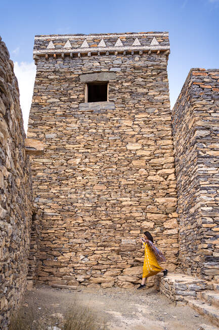 Mujer distante en ropa colorida caminando entre antiguas paredes de edificios históricos de Marble Village en Al Bahah ubicados en terreno de montaña en Arabia Saudita - foto de stock