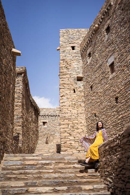 Снизу монументального древнего здания с удаленной туристкой, выходящей из дверей в желтом платье, наслаждаясь жарким солнечным днем в Мраморной деревне в Аль-Баха — стоковое фото