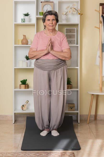 Mujer anciana concentrada en ropa deportiva de pie en la estera cerca de estantes con las manos dobladas con los ojos cerrados durante la práctica de yoga en casa - foto de stock