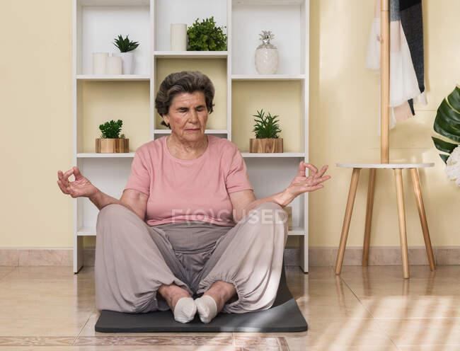 Концентрированная старшая женщина в активной одежде сидит на коврике рядом с полками и медитирует с закрытыми глазами во время занятий йогой дома — стоковое фото