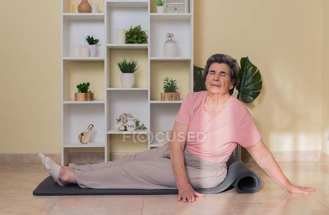 Вид сбоку сфокусированной пожилой женщины в активной одежде, сидящей на коврике рядом с полками с горшечными растениями в комнате и делающей упражнения на растяжку во время занятий йогой — стоковое фото