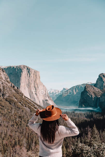 Back view of unrecognizable female traveler in hat standing on hill covered with forest and admiring picturesque scenery with granite cliffs in sunny day in Yosemite National Park in California — Stock Photo