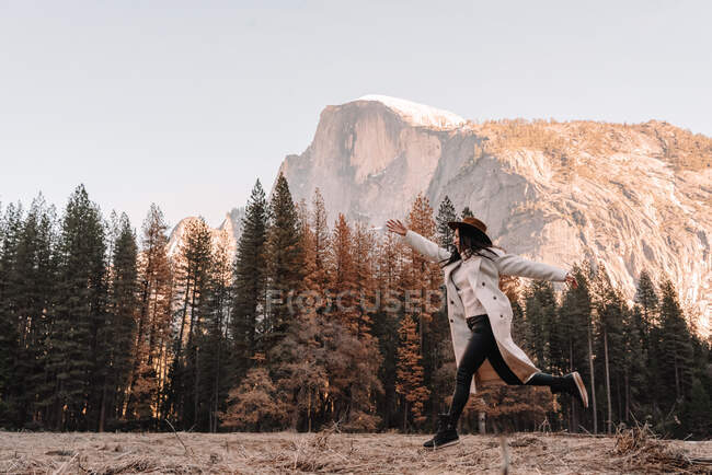 Full body side view of carefree young female traveler in stylish outfit running and jumping on meadow against pine trees and majestic rocky cliff in sunny spring day in Yosemite National Park in USA — Stock Photo