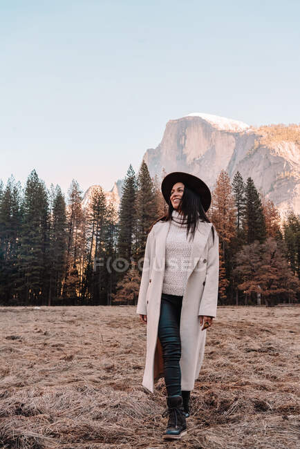 Happy relaxed young female traveler in stylish outfit sitting on stone border against picturesque mountain scenery with rocky cliffs and coniferous forest in Yosemite National Park in USA — Stock Photo