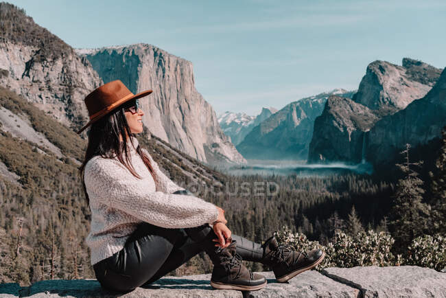 Full body side view of happy relaxed young female traveler in stylish outfit sitting on stone border against picturesque mountain scenery with rocky cliffs and coniferous forest in Yosemite National Park in USA — Stock Photo