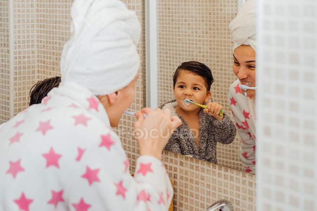 Menino bonito em roupão de banho e mãe sorridente em turbante toalha de pé no banheiro e escovação de dentes — Fotografia de Stock