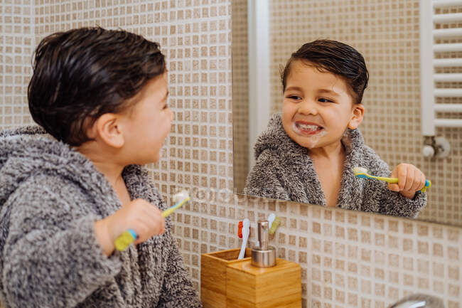 Adorable niño con acogedor albornoz de pie en el baño con cepillo de dientes y mirando en el espejo - foto de stock