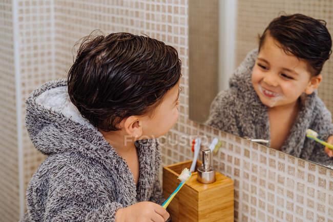 Criança adorável vestindo roupão aconchegante em pé no banheiro com escova de dentes e olhando no espelho — Fotografia de Stock