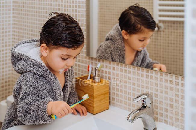 Adorable niño usando acogedor albornoz de pie en el baño con cepillo de dientes - foto de stock
