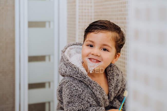 Очаровательный ребенок в удобном халате, стоящий в ванной комнате с зубной щеткой — стоковое фото