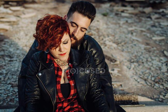 Positiva joven pareja hipster con tatuajes disfrutando del tiempo juntos y abrazándose mientras se pone de pie contra la construcción de piedra en mal estado en un día soleado - foto de stock