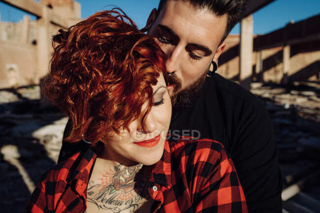 Positif jeune couple hipster avec des tatouages profiter du temps ensemble et étreindre tout en se tenant contre la construction en pierre minable dans la journée ensoleillée — Photo de stock
