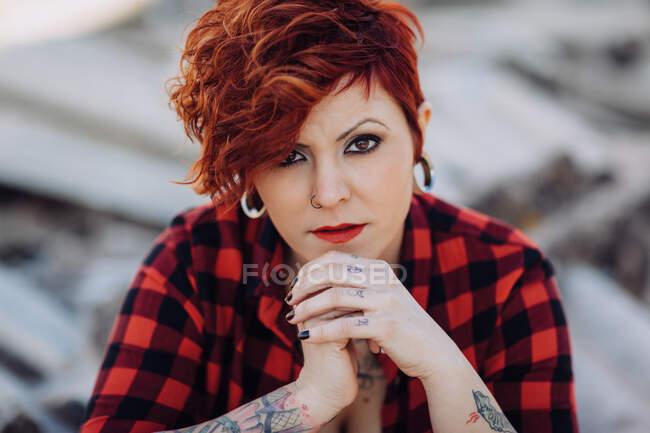 Indipendente elegante giovane donna con taglio di capelli alla moda e tatuaggi indossa camicia a scacchi casual guardando la fotocamera mentre in piedi contro edificio sfocato shabby — Foto stock