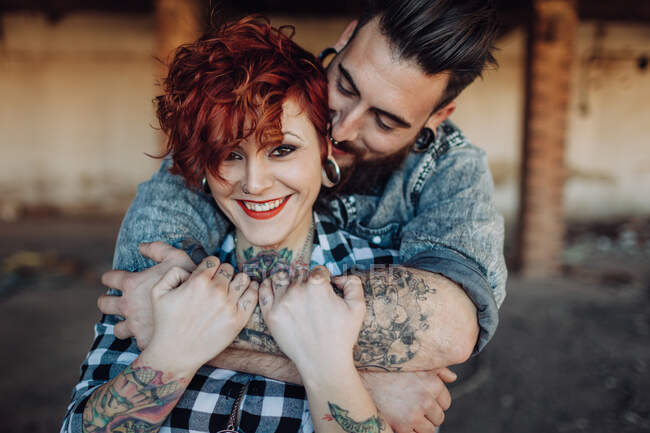Positive young hipster couple with tattoos enjoying time together and hugging while standing against shabby stone construction in sunny day — Stock Photo