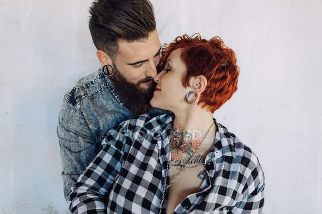 Позитивная молодая хипстерская пара с татуировками, наслаждающаяся временем вместе и обнимающаяся, стоя против обветшалого каменного строительства в солнечный день — стоковое фото