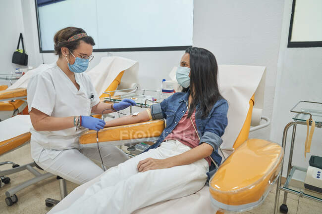 Female medical specialist in latex gloves performing injection with syringe to anonymous patient during procedure of blood transfusion in hospital — Stock Photo