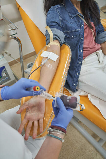 From above of crop female nurse in protective gloves with bag of blood in hand working with patient during procedure of blood donation in modern medical center — Stock Photo