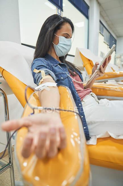 Vista lateral de ángulo bajo de la mujer joven en el teléfono inteligente de navegación máscara protectora durante el procedimiento de transfusión de sangre en el hospital - foto de stock