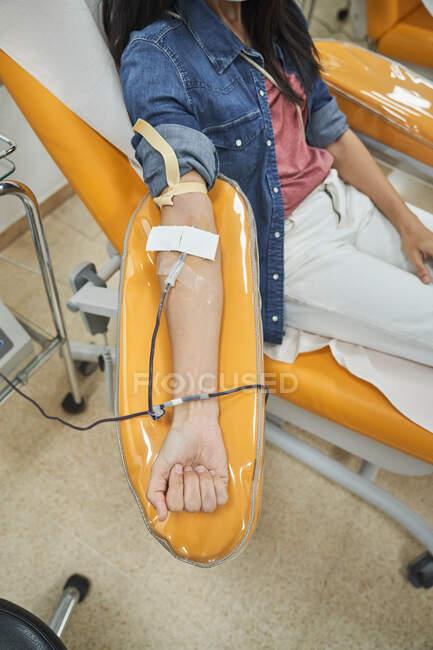 Низкий угол обзора молодой женщины в защитной маске, просматривающей смартфон во время процедуры переливания крови в больнице — стоковое фото