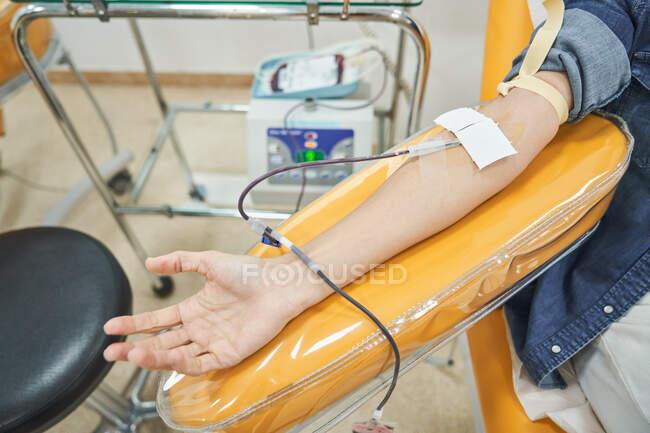 Cultivo voluntario femenino anónimo donando sangre para salvar la vida en el centro de transfusión de sangre moderna - foto de stock