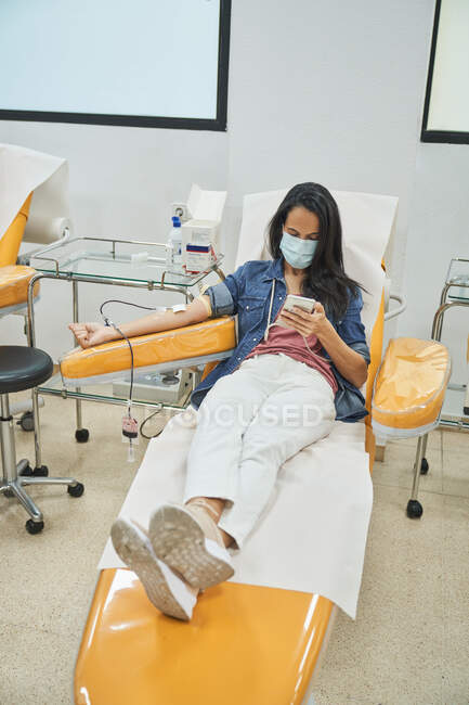 Low angle side view of young female in protective mask browsing smartphone during procedure of blood transfusion in hospital — Stock Photo