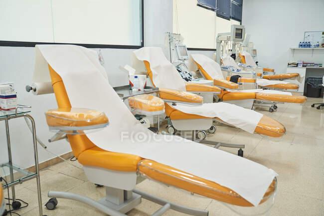 Poltronas médicas vazias preparadas para doadores em moderno centro de transfusão de sangue com equipamentos contemporâneos — Fotografia de Stock