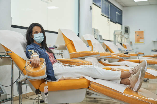 Side view of young woman in protective mask sitting in medical armchair during blood transfusion procedure in contemporary hospital — Stock Photo