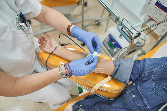 Crop female medical specialist in latex gloves performing injection with syringe to anonymous patient during procedure of blood transfusion in hospital — Stock Photo