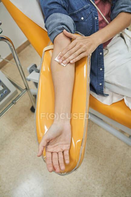 Desde arriba de la cosecha donante femenina anónima con parche en la mano sentado en silla médica después del procedimiento de transfusión de sangre - foto de stock
