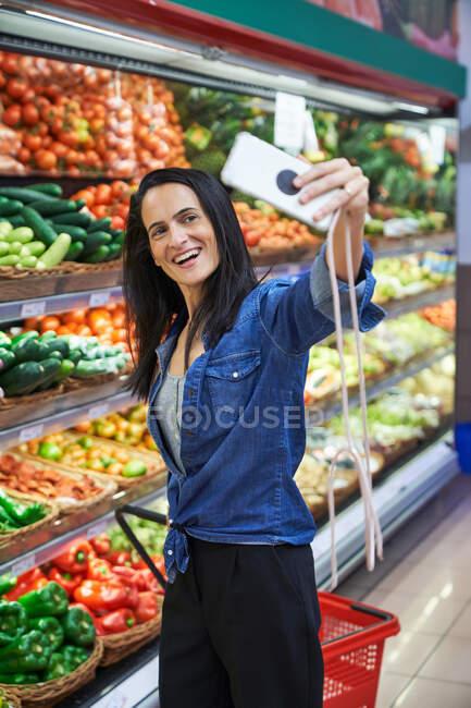 Morena mulher tirar uma foto na mercearia em um supermercado — Fotografia de Stock
