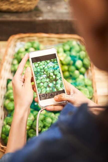 Femme prenant une photo avec le mobile à certains légumes dans le supermarché — Photo de stock