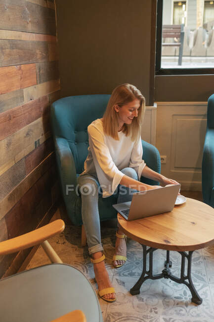Young blonde happy female freelancer in casual clothes having tasty hot drink while sitting at round wooden table and using netbook in light modern cafe — Stock Photo