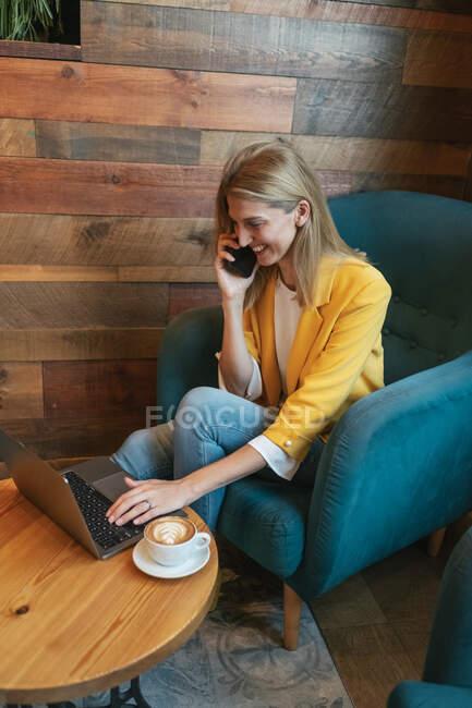 Hoher Winkel der lachenden erwachsenen Freiberuflerin in lässiger Kleidung, die sich auf den Laptop-Bildschirm konzentriert und tippt, während sie in einem weichen blauen Sessel am runden Holztisch mit einer Tasse Heißgetränk sitzt und in einem modernen Café telefoniert — Stockfoto
