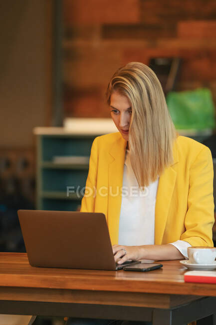 Focused adult businesswoman in formal wear looking away while sitting at wooden table with laptop in contemporary cafe shop — Stock Photo