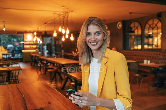 Joyful adult female in elegant vivid yellow jacket smiling at camera while sitting at wooden table and interacting with smartphone against blurred interior of contemporary restaurant — Stock Photo
