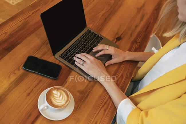 Сверху обрезали неузнаваемую молодую фрилансершу в повседневной одежде с вкусным горячим напитком, сидя за деревянным столом и пользуясь ноутбуком в светлом современном кафе — стоковое фото