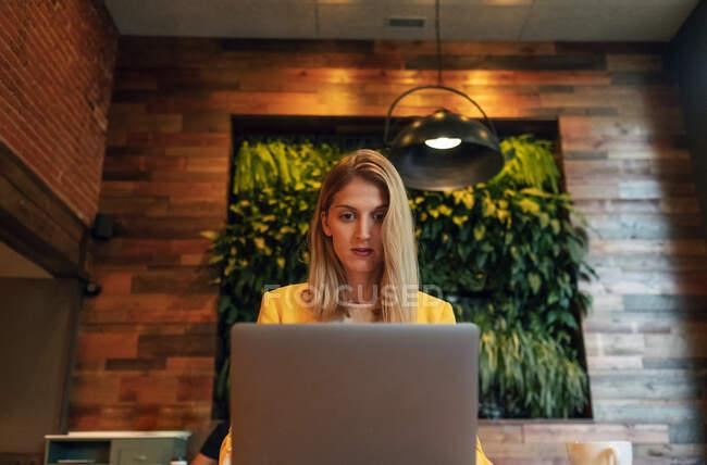 Von unten fokussierte erwachsene Geschäftsfrau in formeller Kleidung, die wegschaut, während sie an einem Holztisch mit Laptop in einem modernen Café-Shop sitzt — Stockfoto
