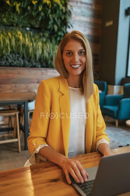 Adult overjoyed businesswoman in formal wear looking at camera and smiling while sitting at wooden table with laptop in contemporary cafe shop — Stock Photo