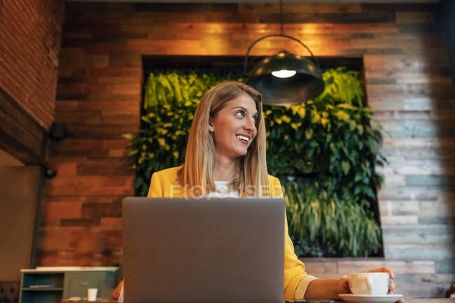 Adult overjoyed businesswoman in formal wear looking away and smiling while sitting at wooden table with laptop in contemporary cafe shop — Stock Photo