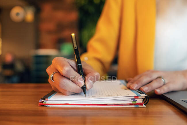 Crop unrecognizable businesswoman in elegant colorful clothes writing with pen in notebook while sitting at wooden table and using laptop in light contemporary office — Stock Photo