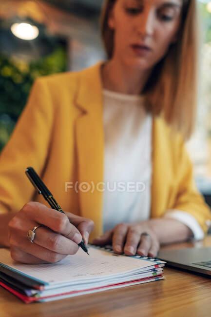 Verschwommene Geschäftsfrau in eleganter bunter Kleidung, die mit Stift in Notizbuch schreibt, während sie am Holztisch sitzt und Laptop im hellen modernen Büro benutzt — Stockfoto