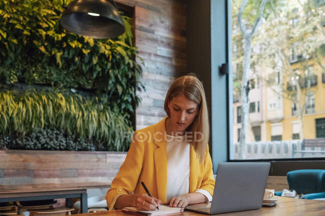 Businesswoman in colorful clothes writing with pen in notebook while sitting at wooden table and using laptop in light contemporary coffee shop — Stock Photo